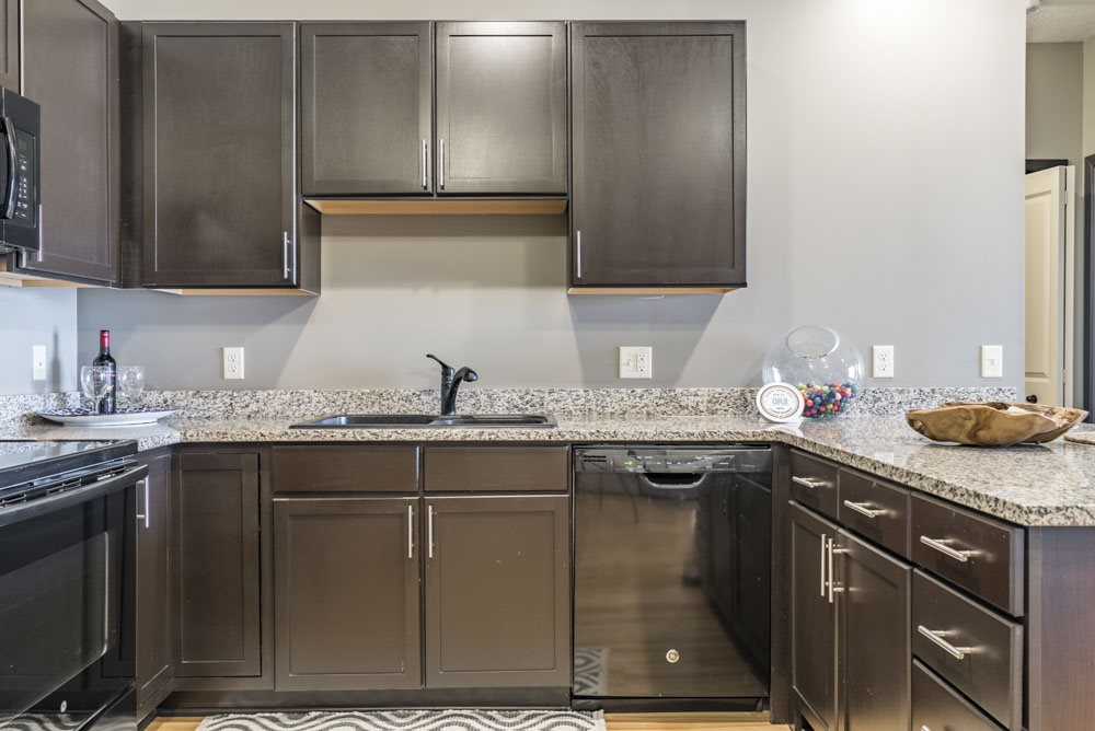 Style A design with dark cabinetry and light granite countertops https://www.dropbox.com/s/xwctcaxy3c9d22p/The%20Villas%20at%20Mahoney%20Park-November%202018-FINAL%20WITH%20BLEED.pdf?dl=0