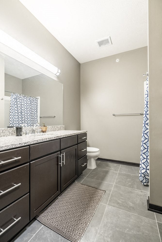 Bathroom with granite countertops and tile flooring at The Flats at 84 in southeast Lincoln NE 68516