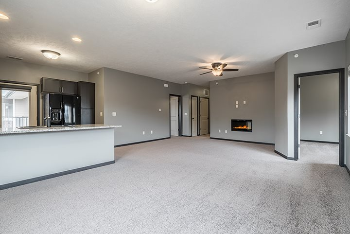 Interiors-Living room with electric fireplace and ceiling fan at The Villas of Omaha at Butler Ridge in Omaha Nebraska