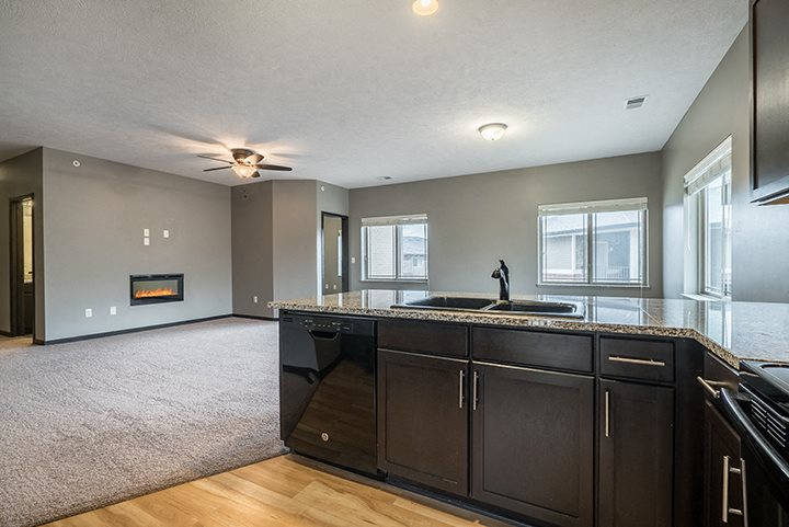 Interiors- A kitchen that opens up to a large living space at the Villas of Omaha at Butler Ridge in Omaha Nebraska