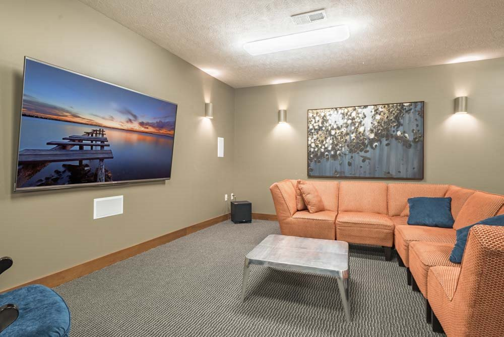 Theater room with large TV and couches at Villas of Omaha townhome apartments in northwest Omaha NE 68116