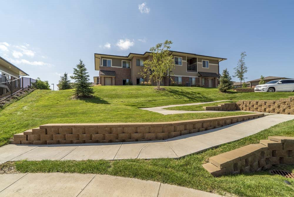 Villa building on top of green hill at Villas of Omaha townhome apartments in northwest Omaha NE 68116
