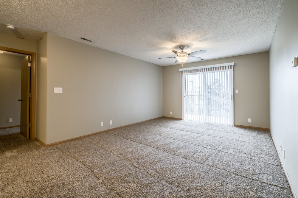 Empty living room with carpet, ceiling fan, and sliding glass door