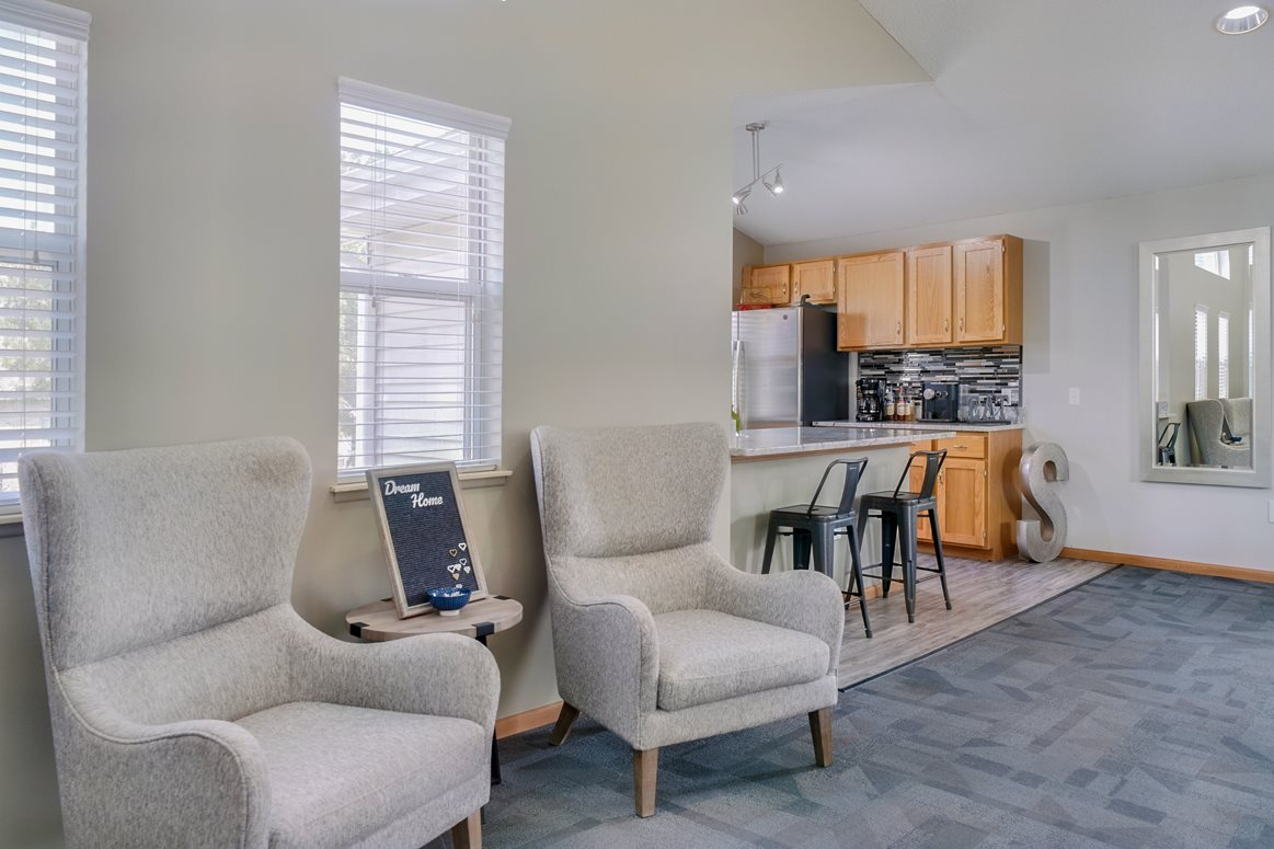 Lounge space with chairs near the kitchen in the clubhouse at Skyline View