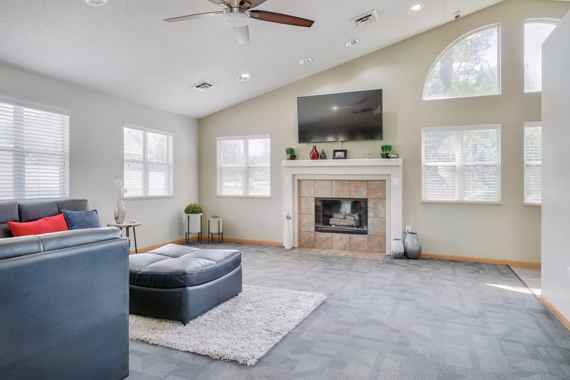 Lounge space with sectional couch and fireplace with TV mounted above it