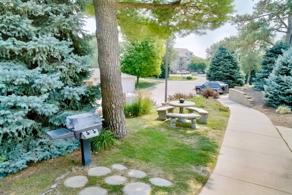 Outdoor space with charcoal grill outside of the clubhouse at Skyline View apartments