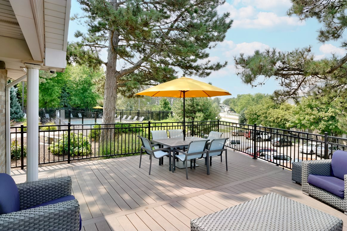 Deck attached to the clubhouse with patio furniture
