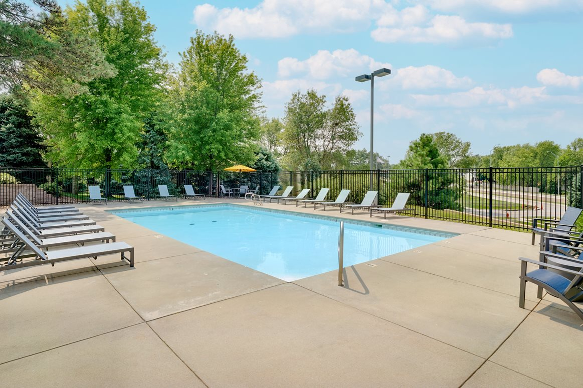Outdoor pool surrounded by trees and landscaping and enclosed by an iron fence