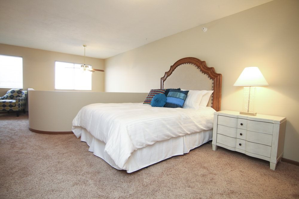 Lofted bedroom with two windows and area over looking living room below