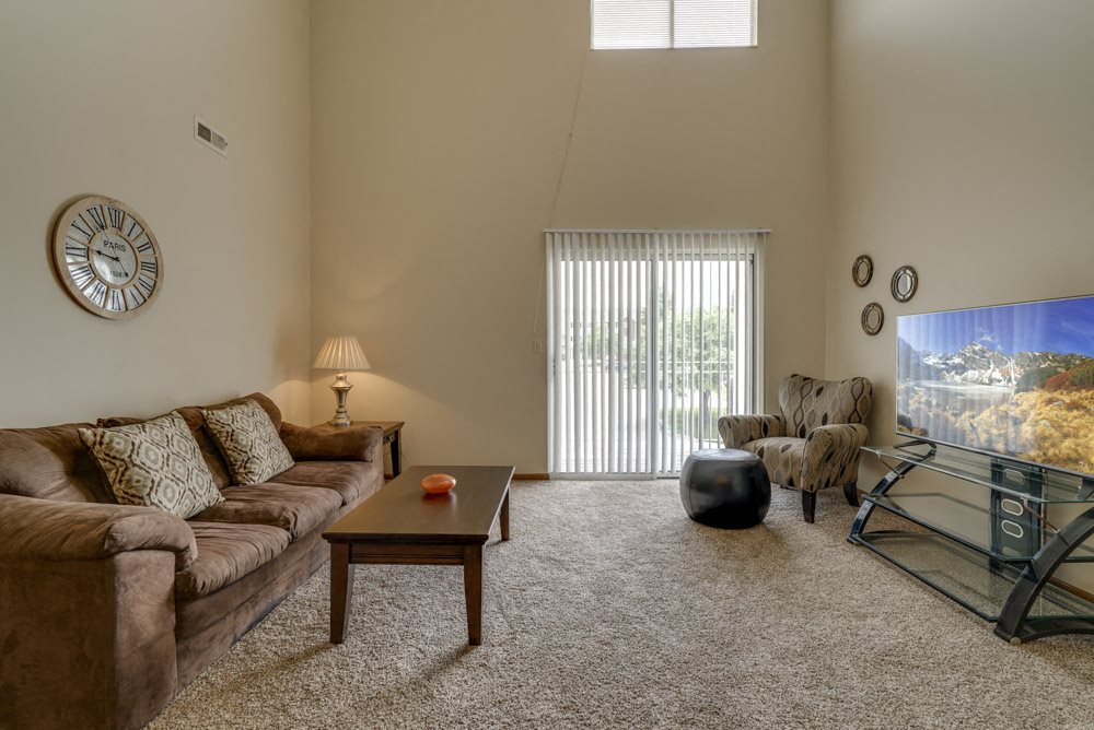 Large windows and sliding doors provide lots of natural lighting in the living space at Pine Lake Heights Apartments
