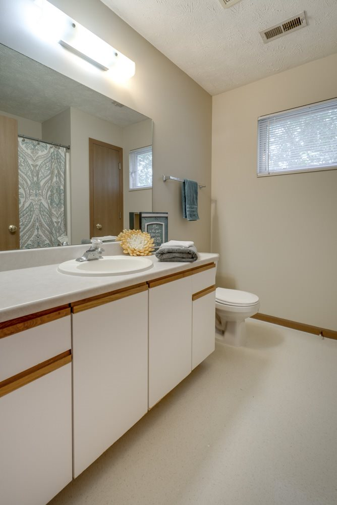 Bathroom with vanity with cabinets for storage at Pine Lake Heights apartments