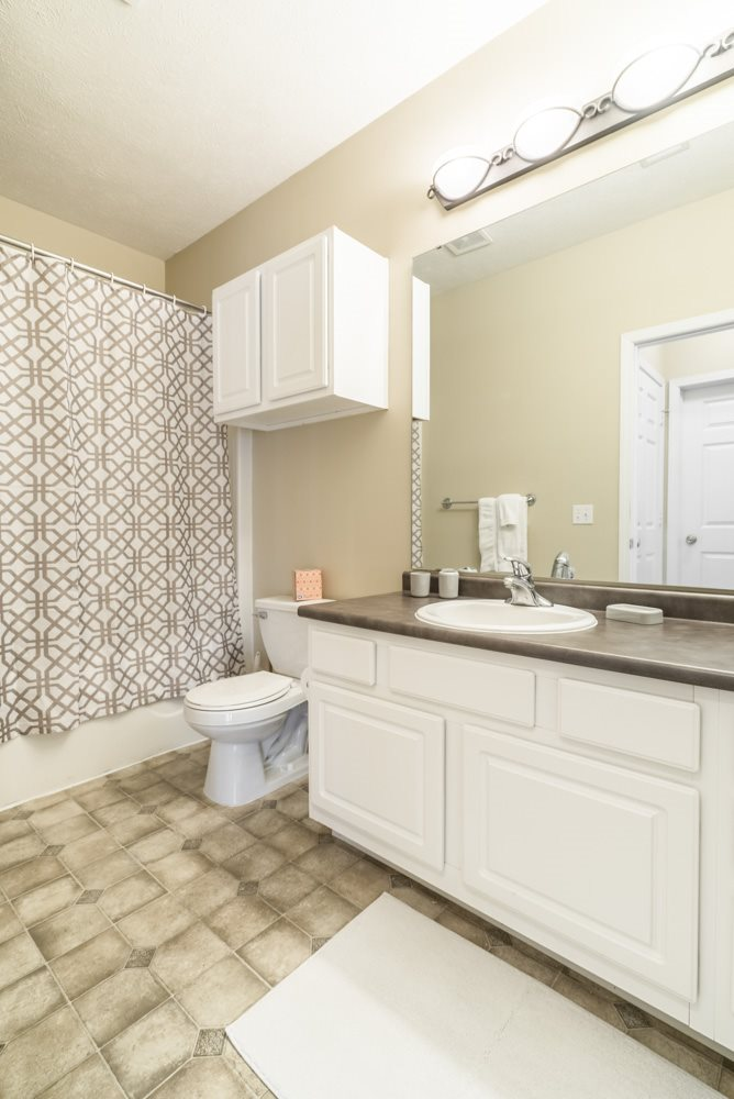 Interiors-Bathroom with white cabinetry and bathtub at Ridge Pointe Villas