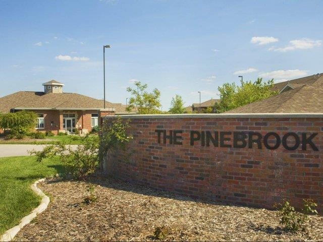 Exteriors-Pinebrook Apartments Sign and Clubhouse View in Lincoln NE