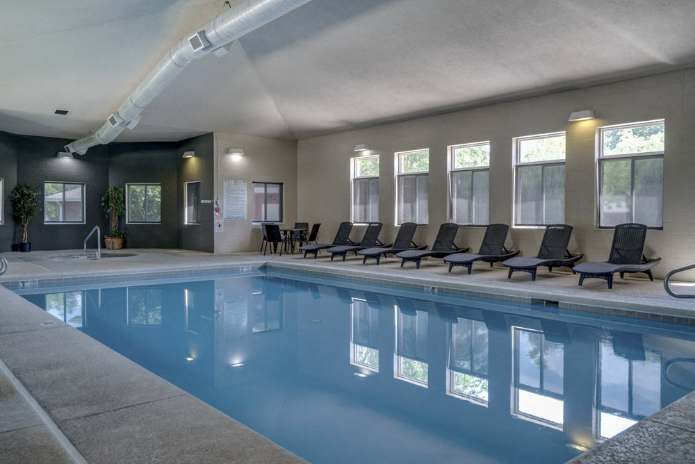 Indoor pool with lounge chairs at Pinebrook Apartments