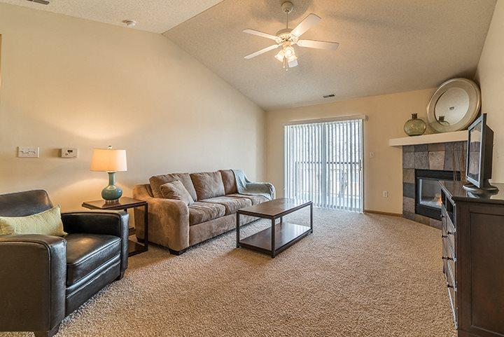 Living room with ceiling fan and lots of natural light at Pinebrook Apartments in Lincoln NE