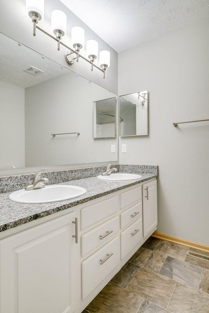 bathroom with dual sinks and white cabinetry at Cascade Pines Duplex and townhomes