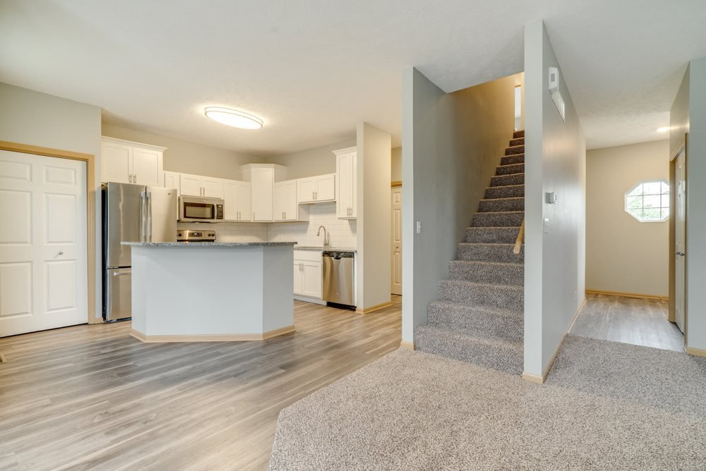 Living and dinning room area with view of kitchen and stairs to the second floor at Cascade Pines Duplex and Townhomes