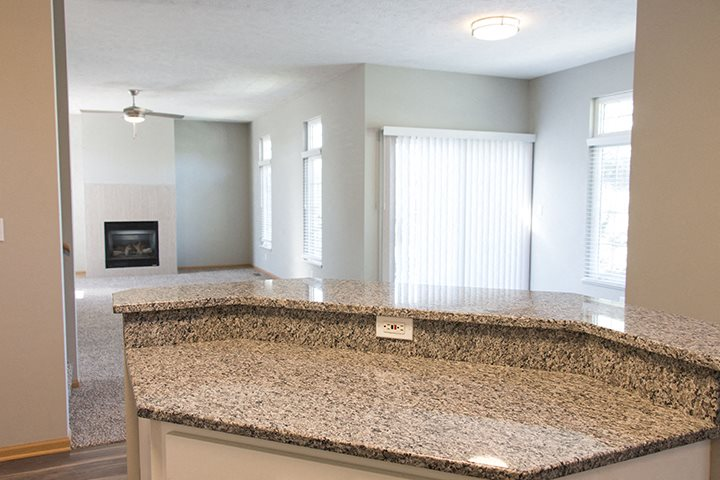 Granite island countertop with open-concept dining living room at Cascade Pines Town-homes Lincoln Nebraska