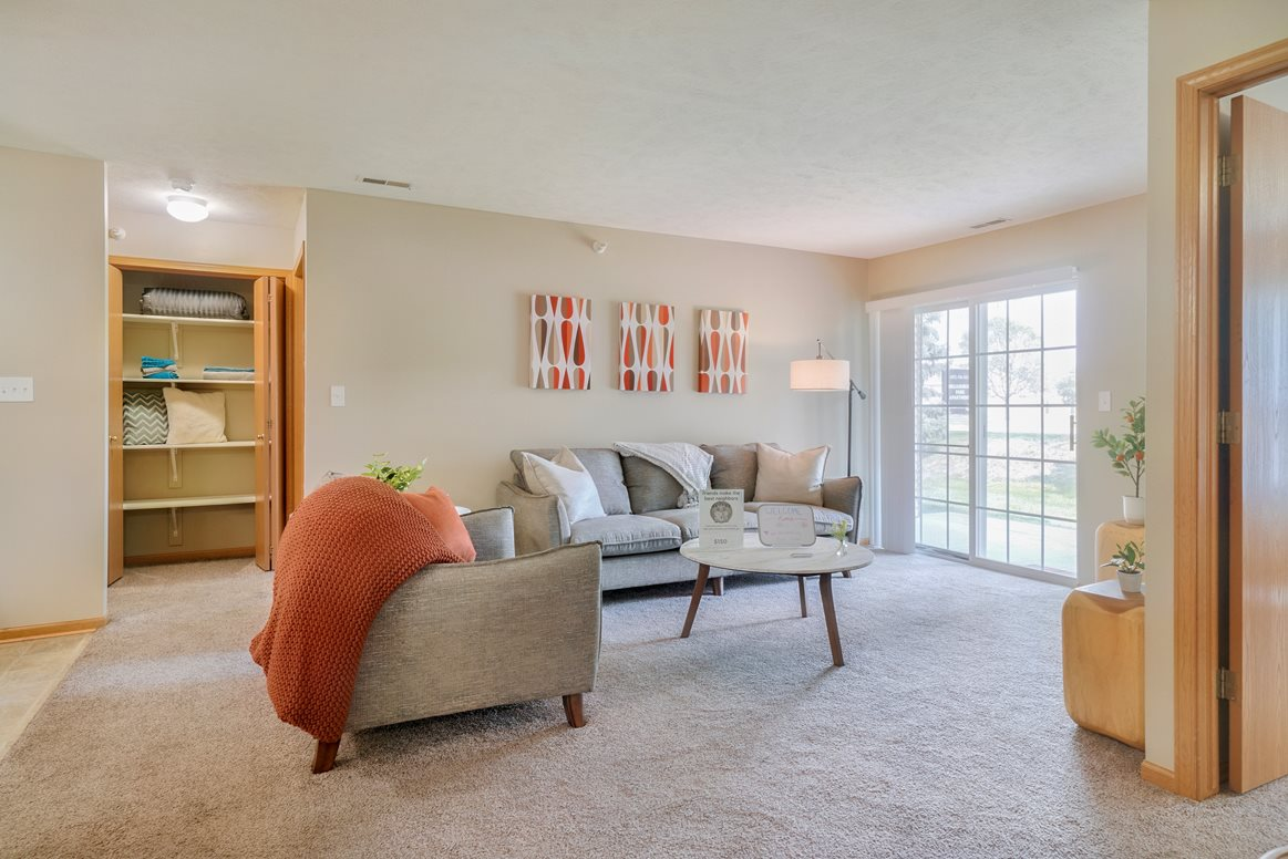 Large open living room with furniture and sliding door that goes out to patio