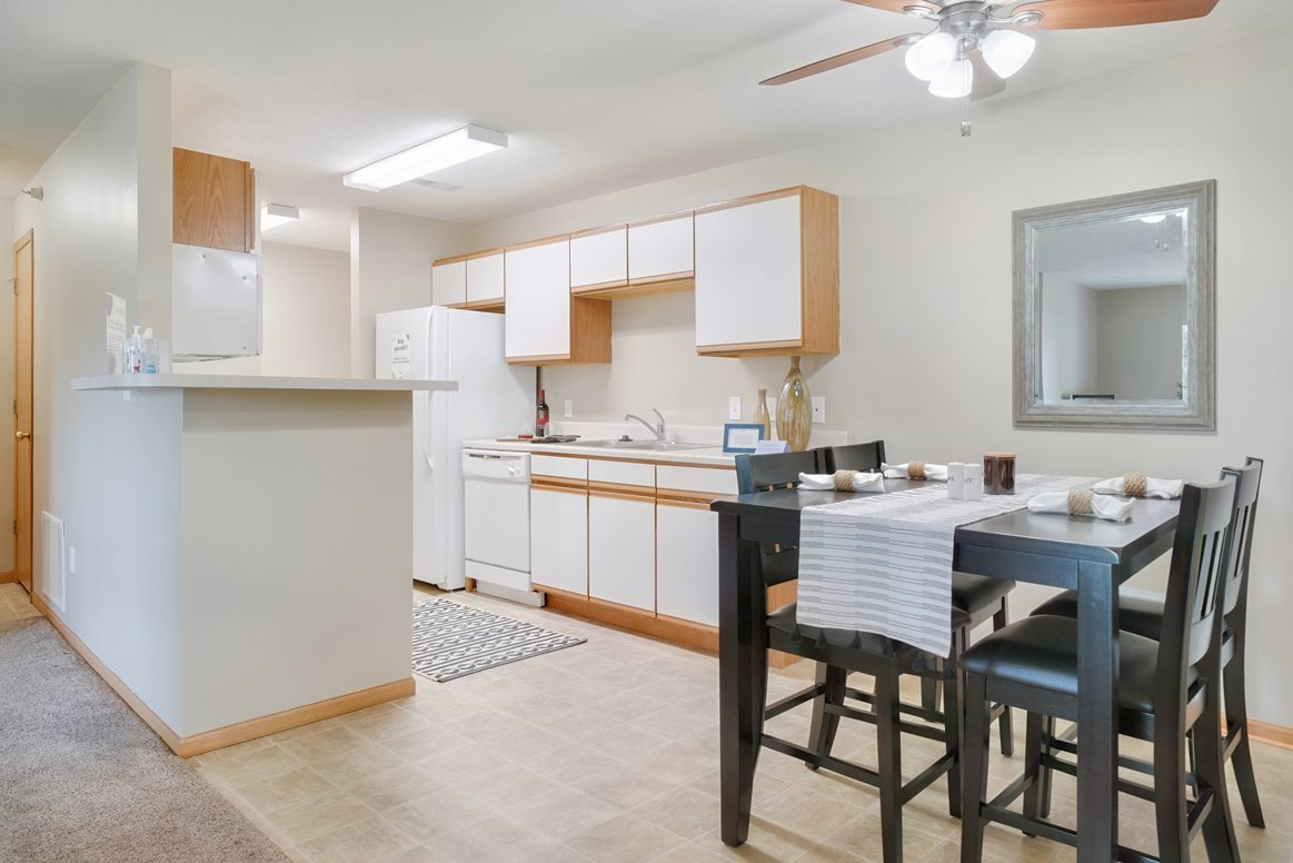 Galley style kitchen with connected dining area with overhead fan