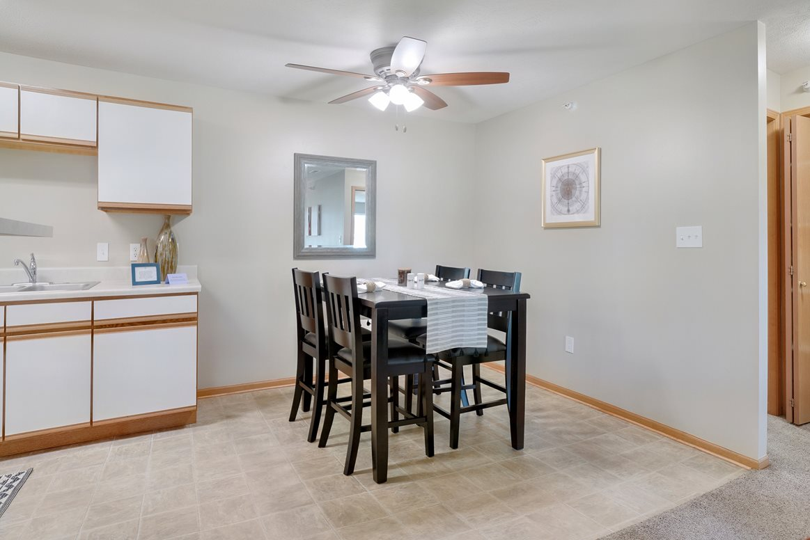 Dining space off of the kitchen that includes a ceiling fan