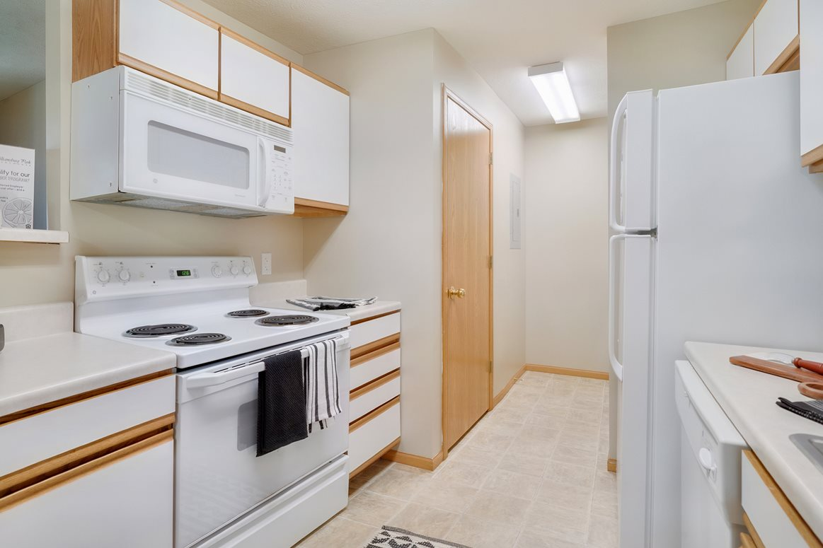 One side of a galley-style kitchen with upper and lower cabinets, stove, and built in microwave