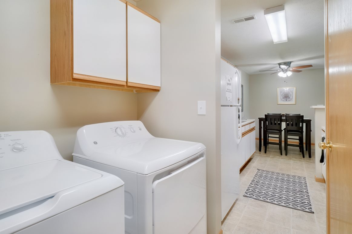 Laundry space off of the kitchen with side by side washer and dryer and cabinet storage above