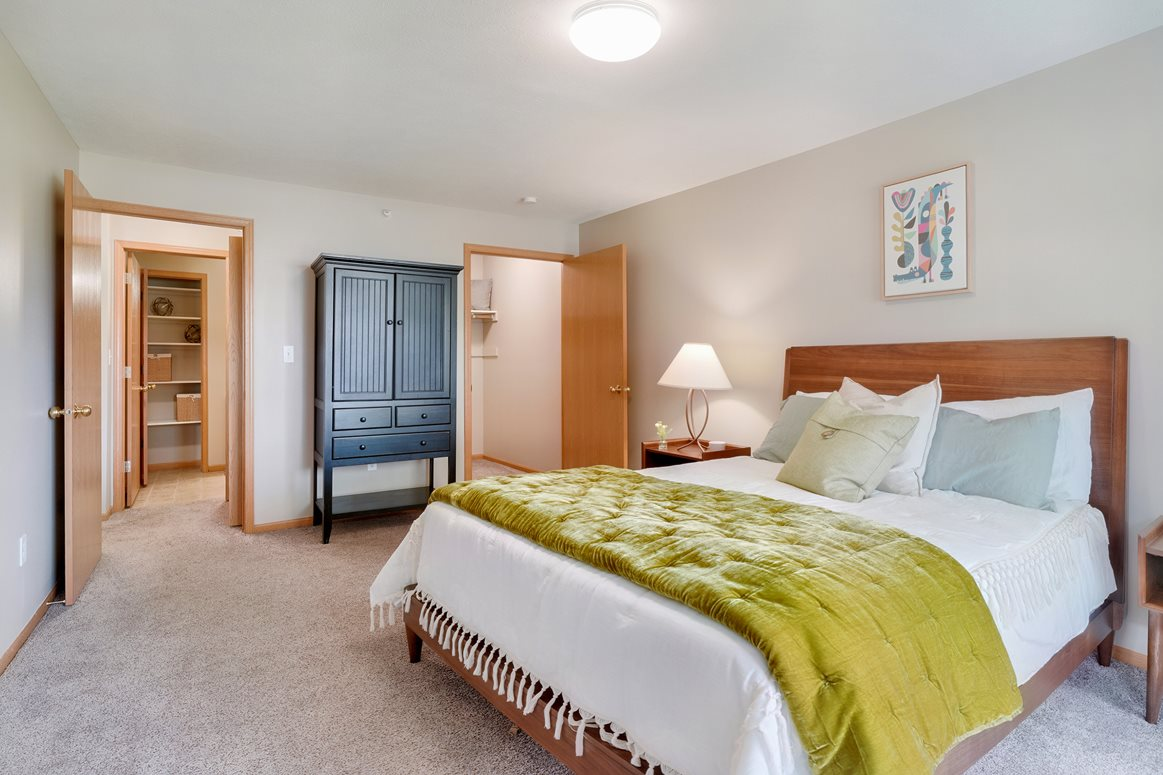 Large bedroom with queen sized bed, night stands and walk in closet