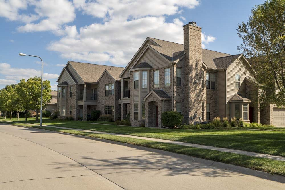 Wide neighborhood street and exterior private apartment entrances at Stone Creek Villas townhomes in west Omaha NE 68116