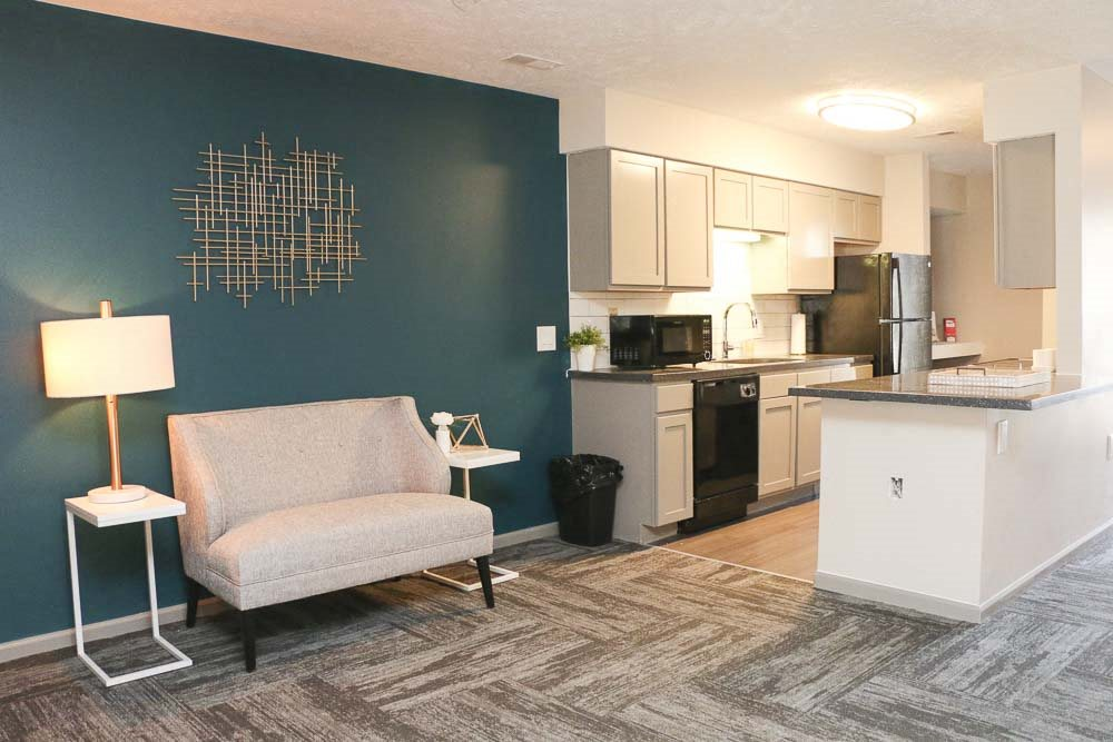 View of sitting chair and kitchen in the clubhouse-Eagle Run Apartments in Omaha NE