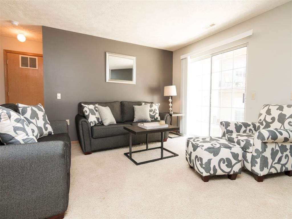 Living room with large sliding doors providing natural light at Eagle Run Apartments in Omaha, NE