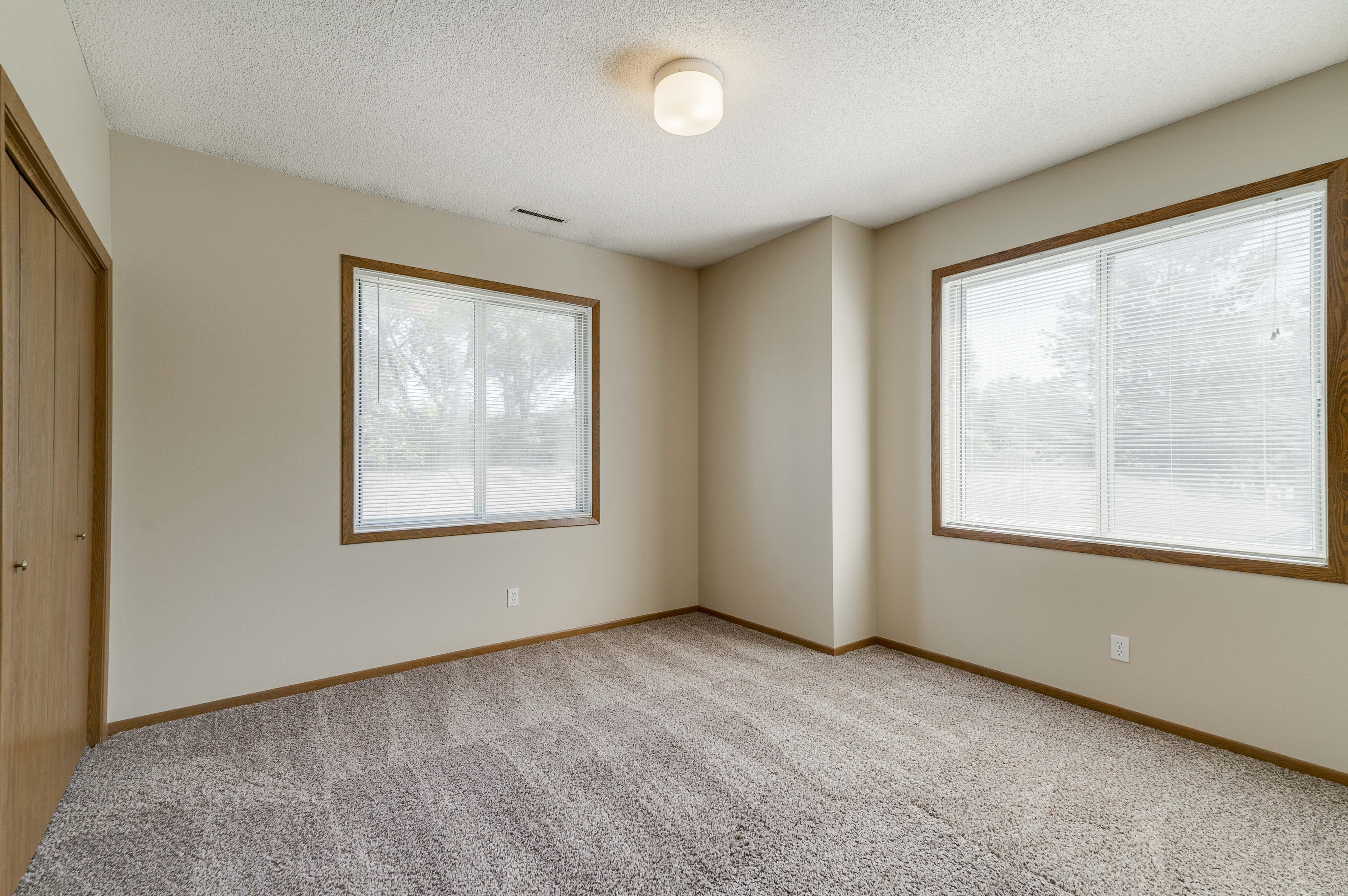Empty bedroom with two large windows and overhead light