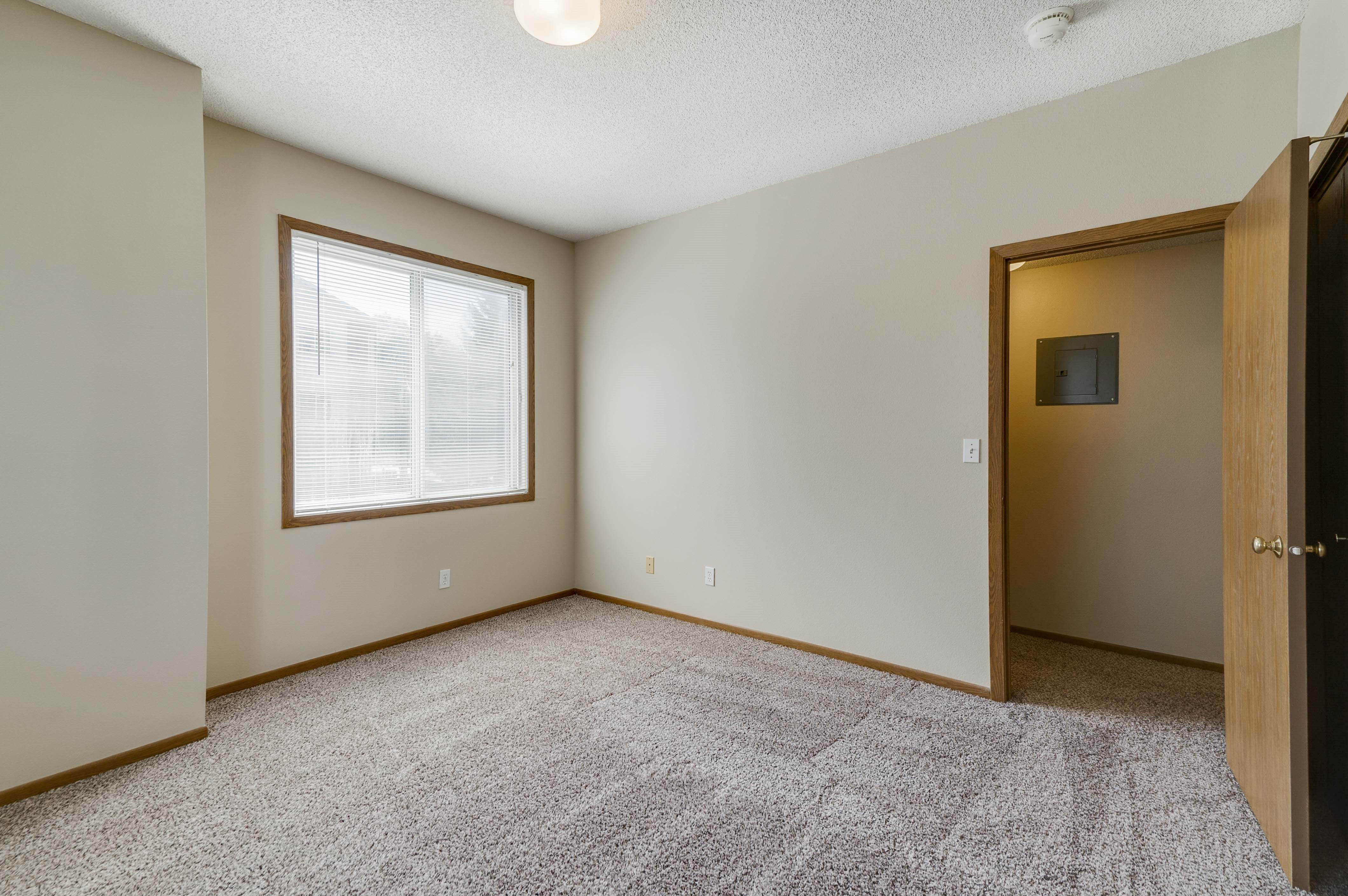 Empty bedroom with two attached closets and one large window