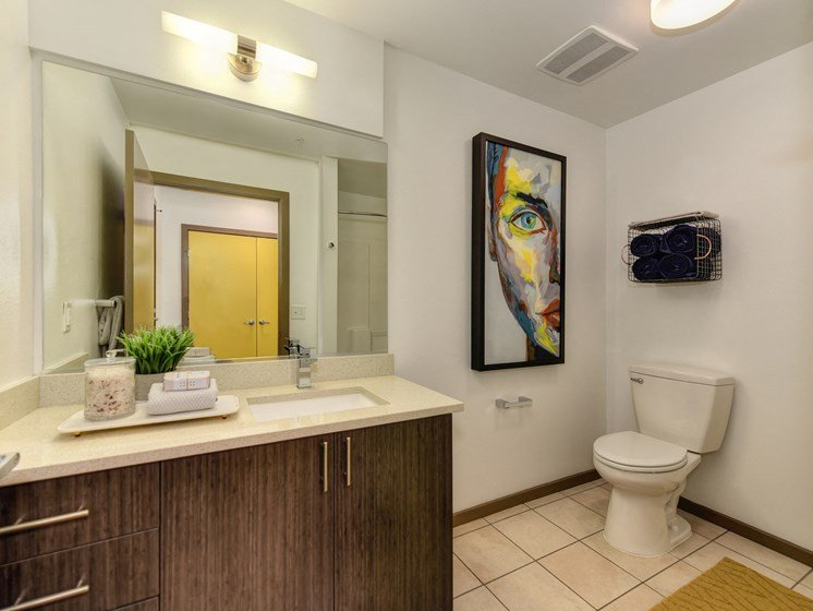 Bathroom with Dark Cabinents, Tiled Floor, Painting of Woman, Vanity and Sink