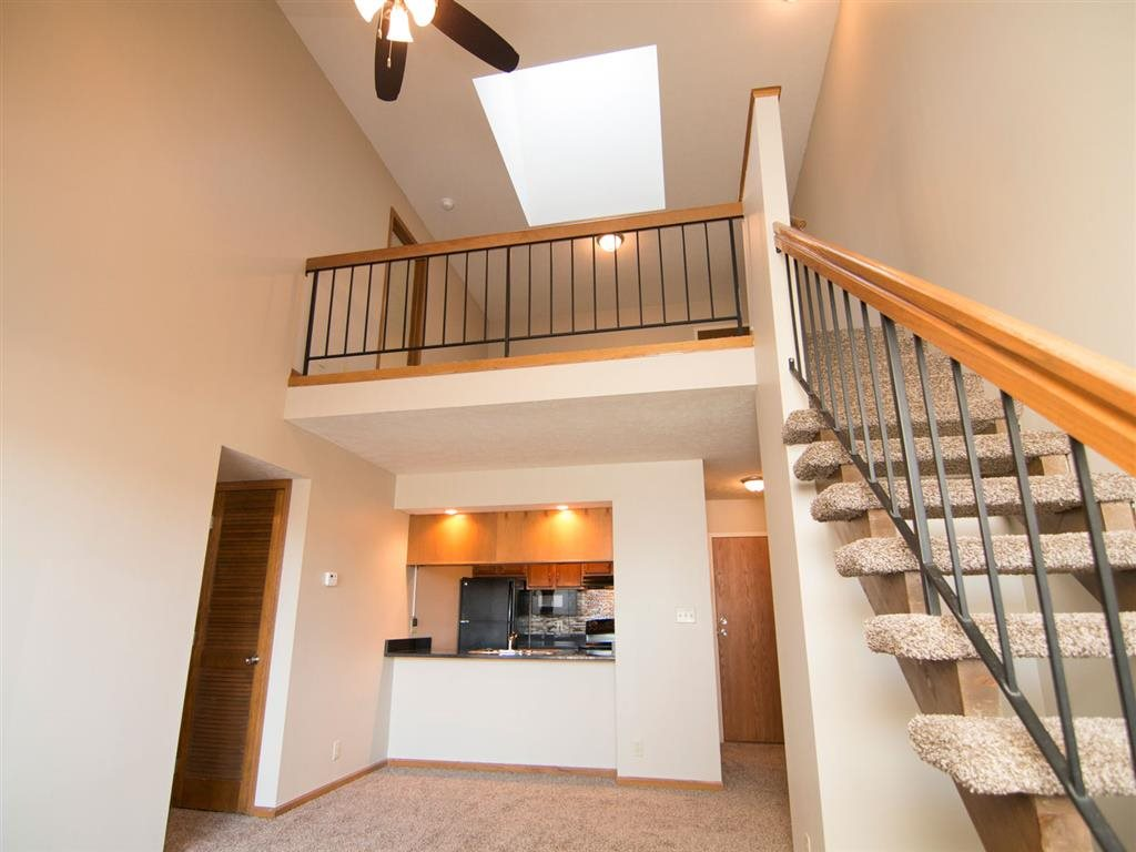 Kitchen and living room with view of stairs to the loft at Fountain Glen Apartments in Lincoln Nebraska
