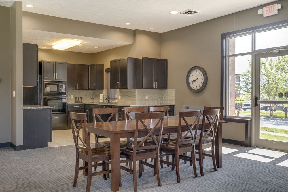 Resident kitchen and table in clubhouse at North Pointe Villas luxury apartments for rent in North Lincoln NE