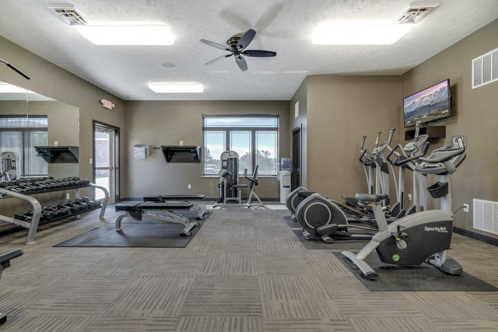 Fitness center with free weights and cardio equipment at North Pointe Villas