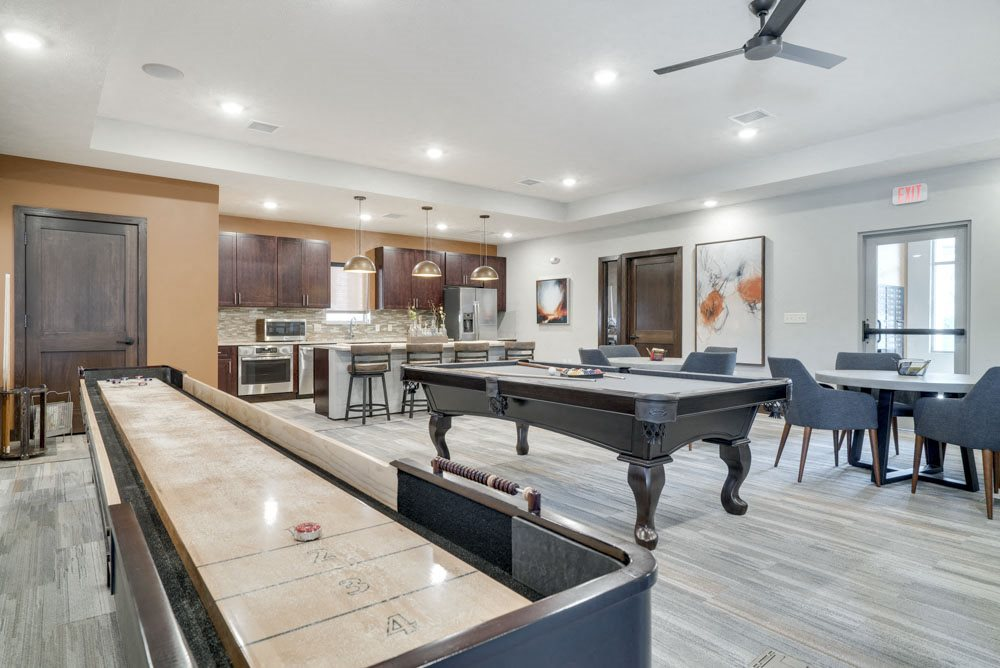 Game room with shuffleboard and pool table at new west clubhouse at North Pointe Villas apartments for rent in North Lincoln NE