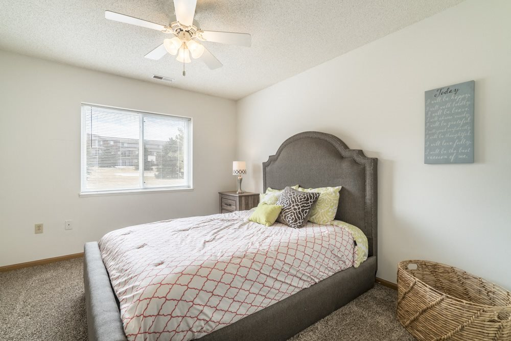 Bedroom with ceiling fan and natural light at Northridge Heights in north Lincoln
