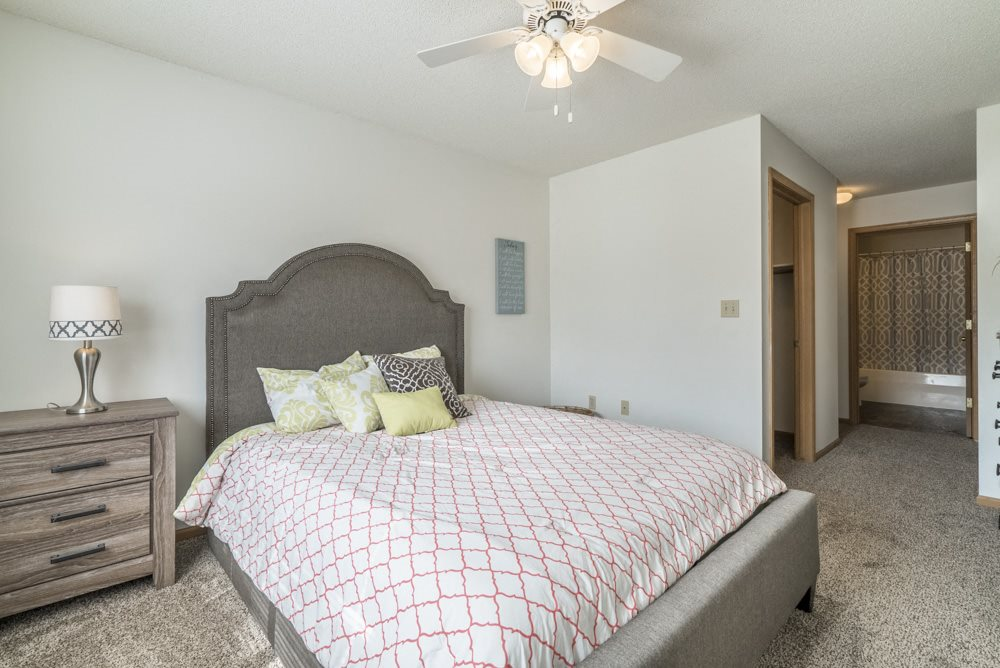 Master bedroom with ceiling fan and attached bathroom at Northridge Heights in Lincoln