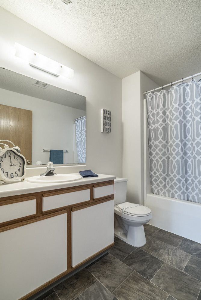 Attached bathroom with cabinet storage space and new flooring at Northridge Heights
