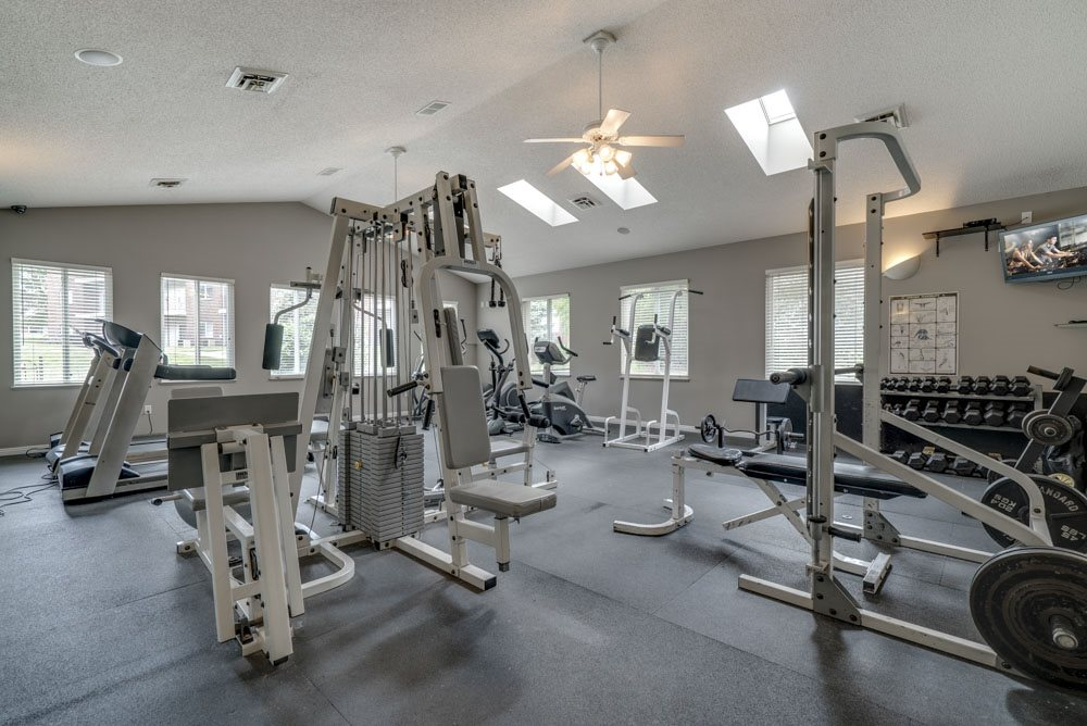 Fitness center with equipment and free weights at Northridge Heights Apartments