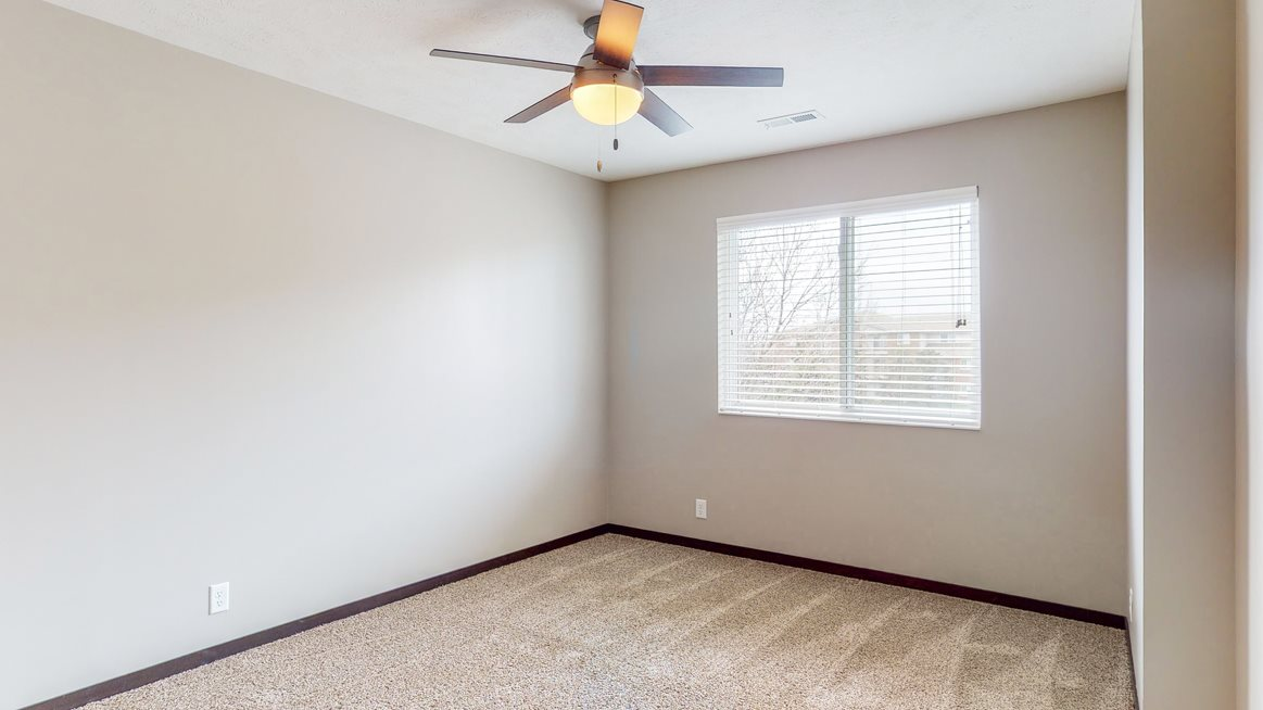 Large renovated bedroom with ceiling fan at Northridge Heights apartments in Lincoln