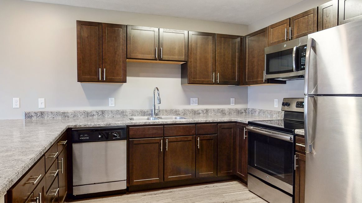 Renovated kitchen with granite counters and new appliances at Northridge Heights Apartments