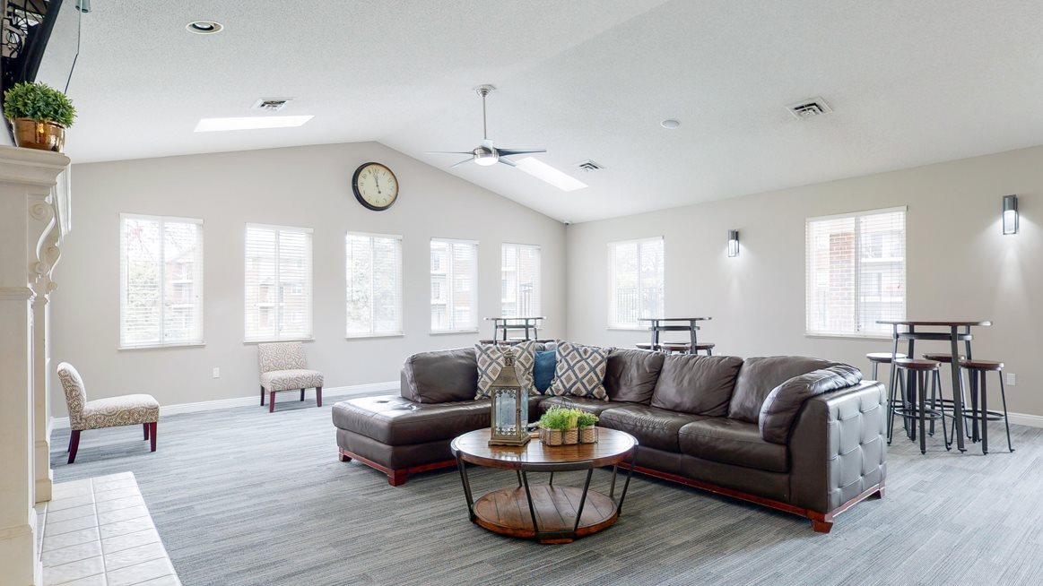 Vaulted ceiling great room with sectional seating around the fireplace and TV