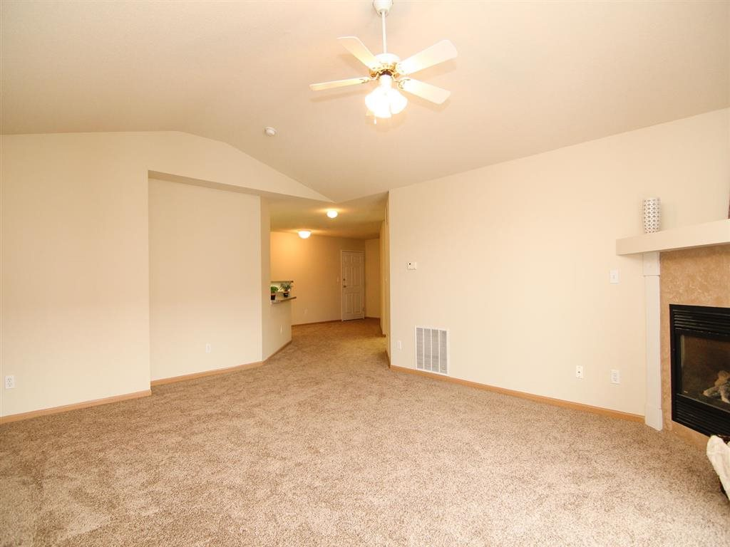 Living room with fire place and ceiling fan at Northbrook Apartments in Lincoln NE