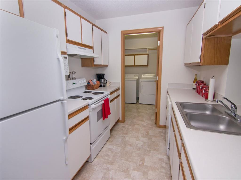 Galley style kitchen with attached laundry at The Northbrook Apartments in Lincoln NE