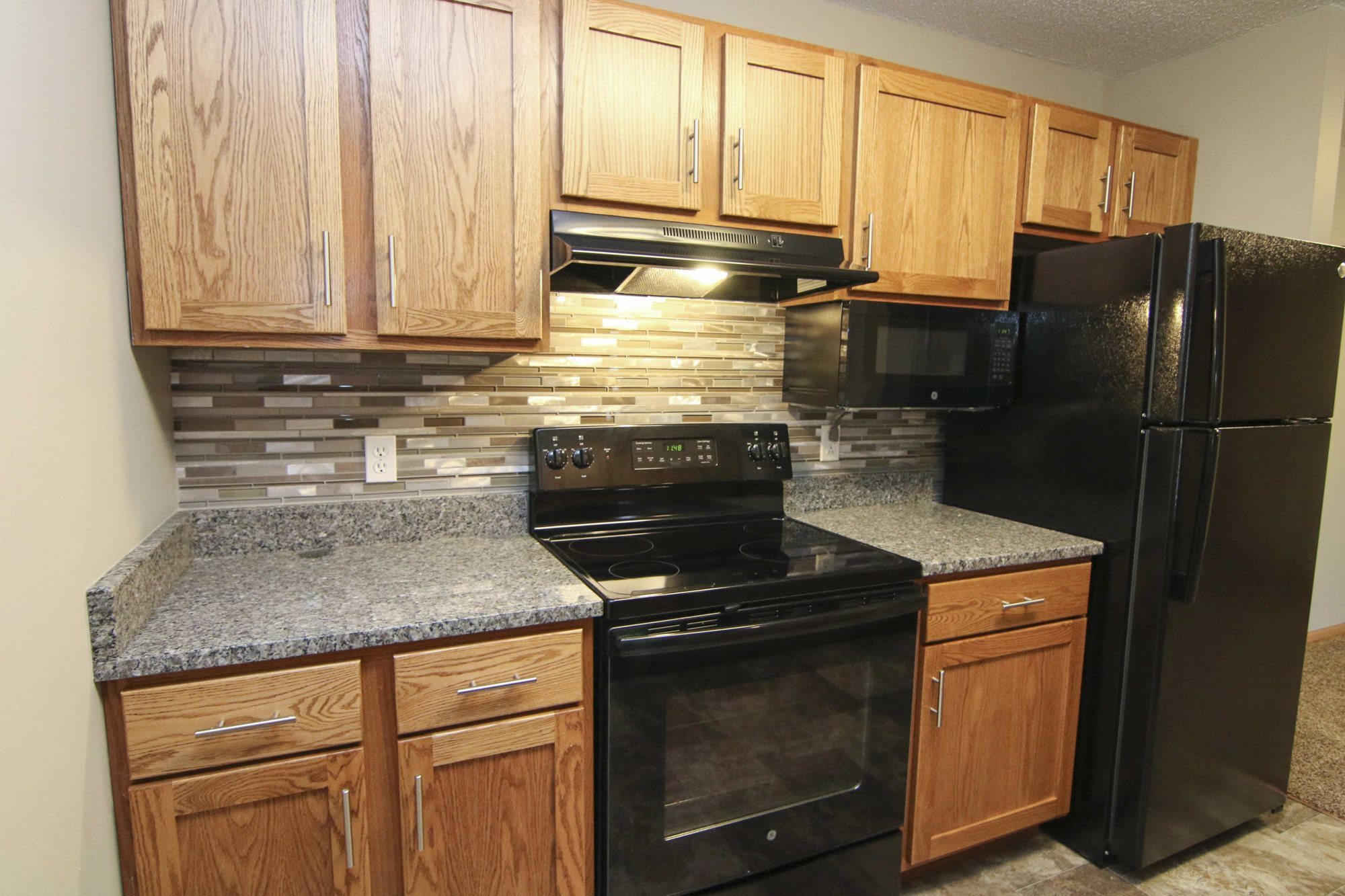 Renovated kitchen with granite counters and new appliances at The Northbrook