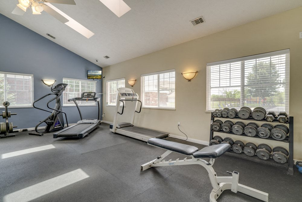 Fitness center with cardio equipment and free weights at The Northbrook Apartments