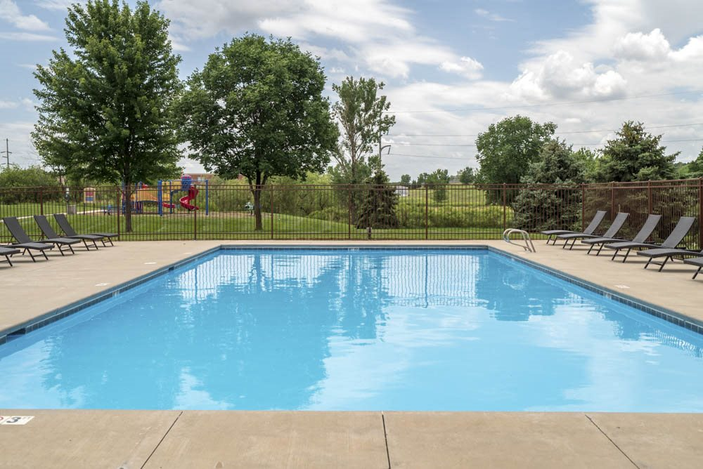 Large outdoor pool with lounge chairs at The Northbrook Apartments